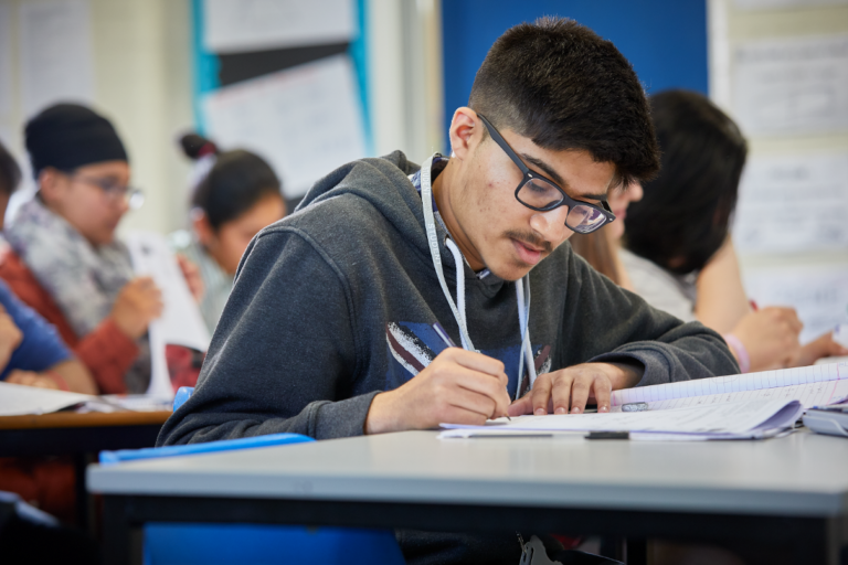 photo of male student sat at desk writing in workbook within classroom