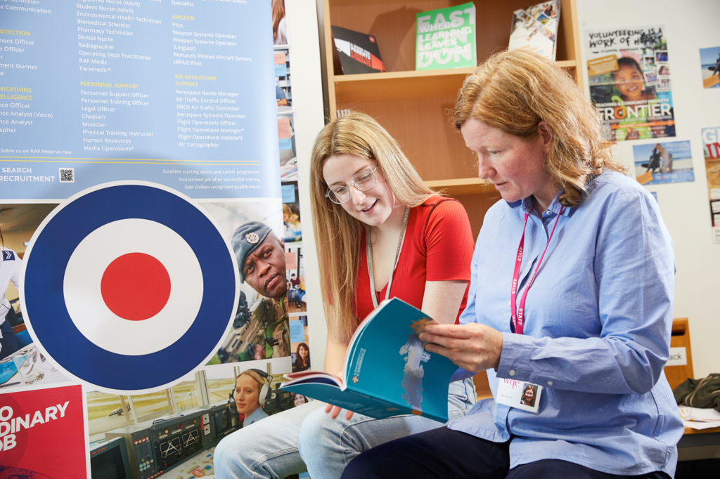 Student and teacher sat reading prospectus in front of Royal Air Force banner
