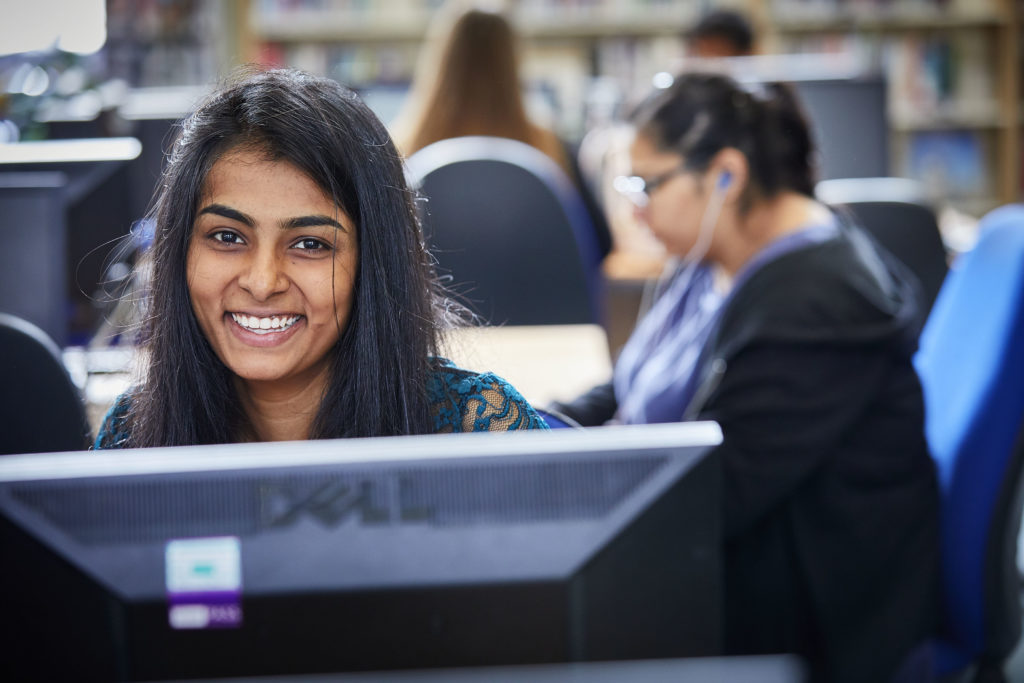 photo of female student smiling in classroom sat at computer