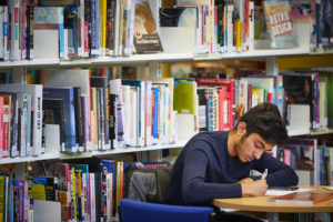 photo of student sat at desk writing in library
