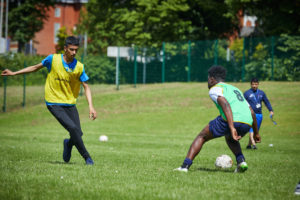 photo of males playing football outside on pitch