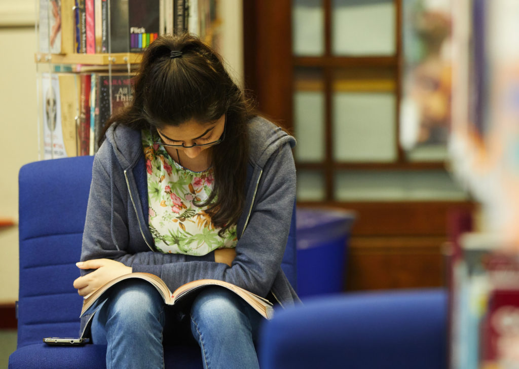 photo of female student sat reading with book on her lap