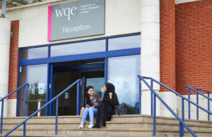 photo of female students sat outside on the steps in front of WQE reception building