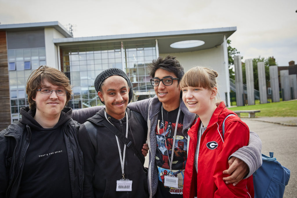 photo showing group of students stood smiling in front of WQE building