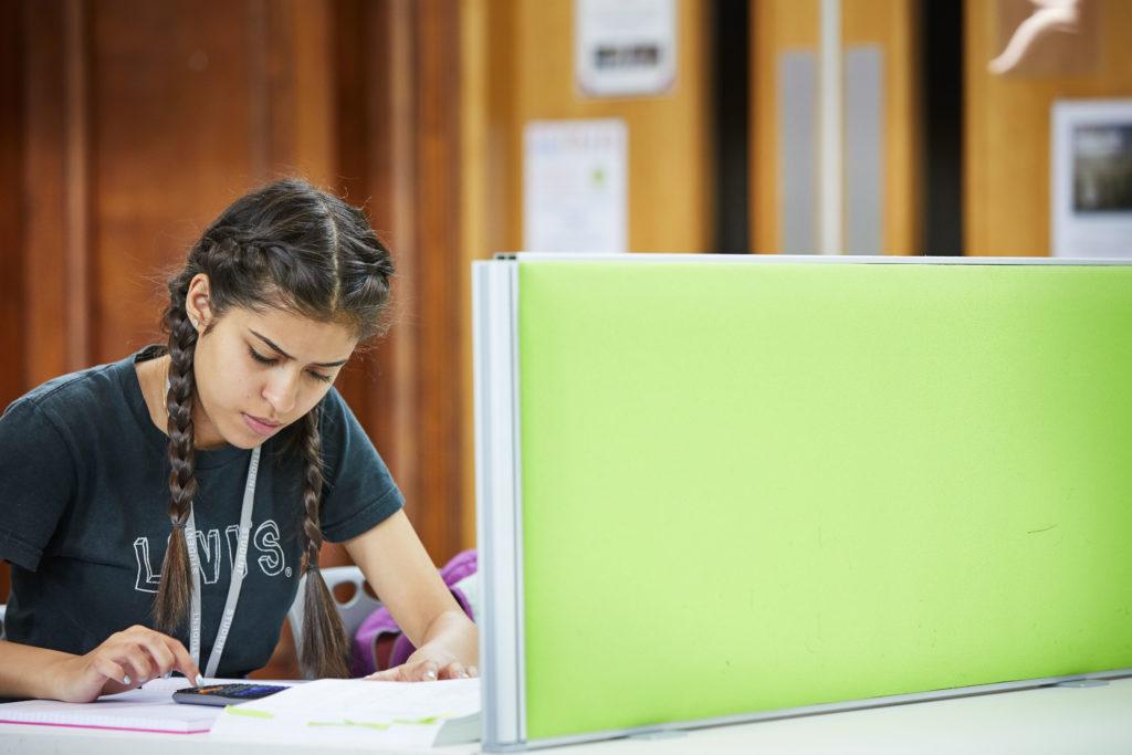 photo of female student sat at desk using calculator