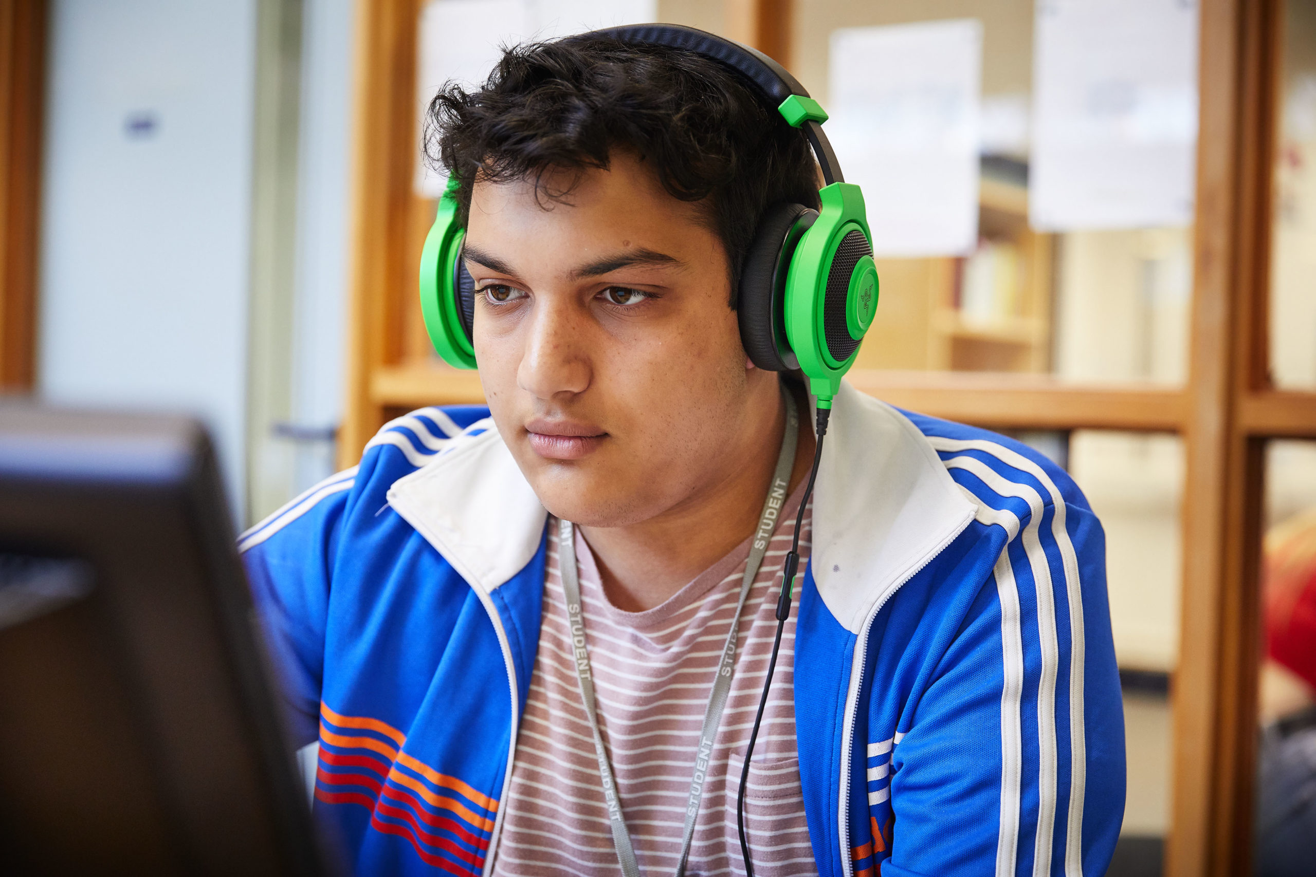 photo of student sat at desk with headphones on