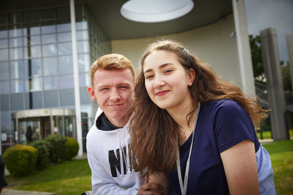 photo of male and female student sat outside building